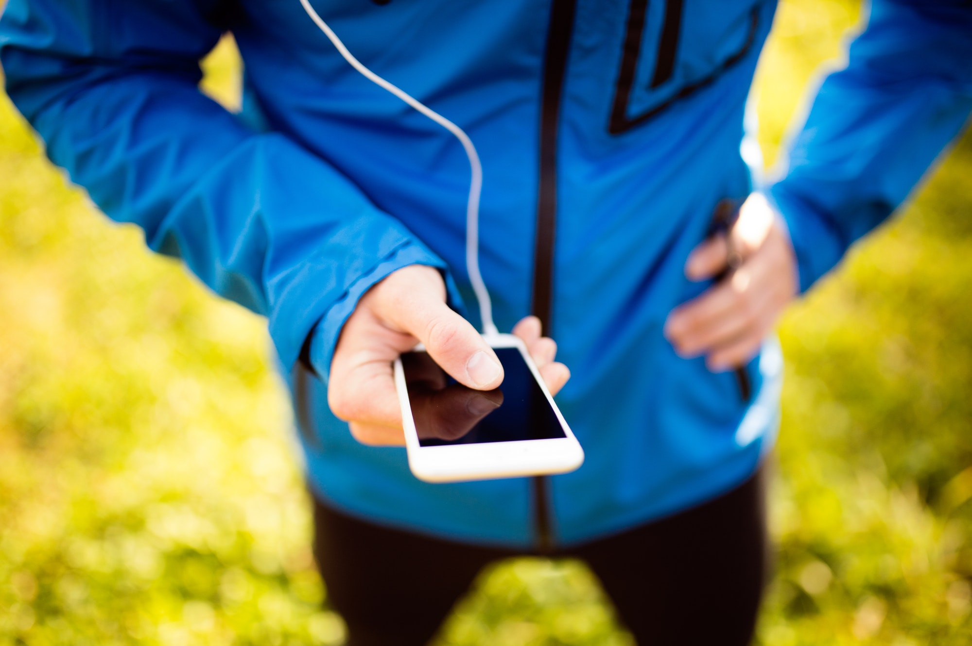Unrecognizable runner with smart phone, using fitness app