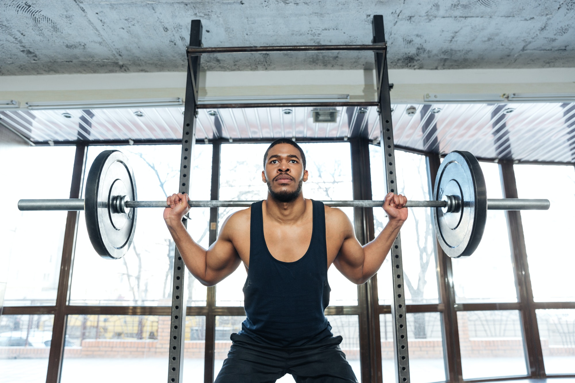 Handsome muscular weightlifter at gym doing squats