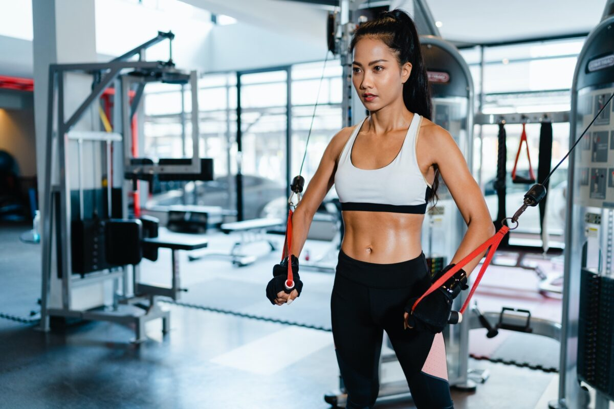 Young Asia lady exercise doing exercise-machine Cable Crossover fat burning.